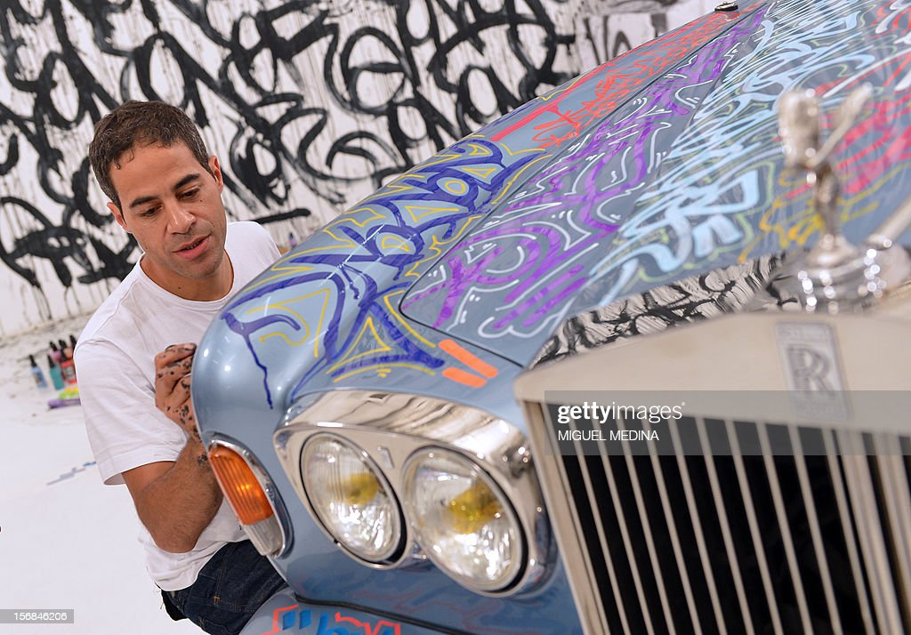 US graffiti artist Jonone performs a painting on a Rolls Royce car owned by former French football player turned actor Eric Cantona during the TV show 'Le grand journal' on a set of French TV Canal+, on November 22, 2012 in Paris during the launching of French charity association Abbe Pierre Foundation's winter campaign.