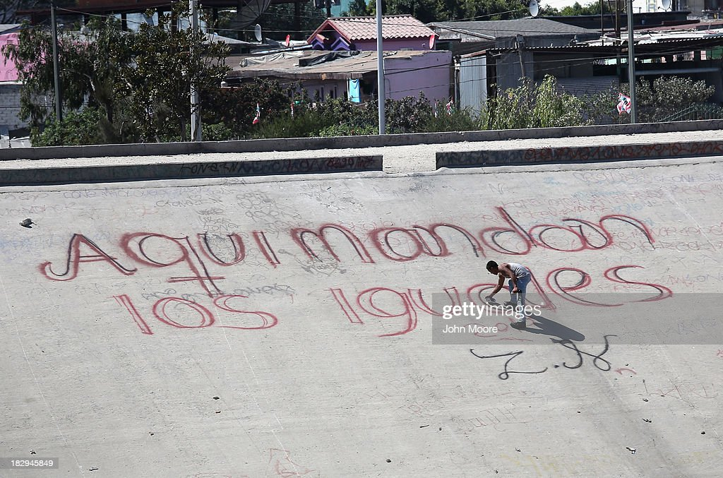 A graffiti artist paints next to the U.S.-Mexico border on October 2, 2013 in Tijuana, Mexico. Despite the U.S. federal shutdown, most U.S. border agents have been categorized as essential personnel and continue working.