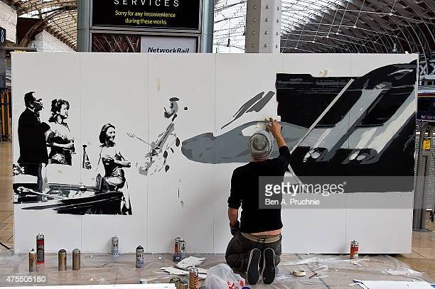 Graffiti artist Tom Cat kneels as he sprays paint creating a dramatic six foot high live art installation alongside at Paddington Central to...