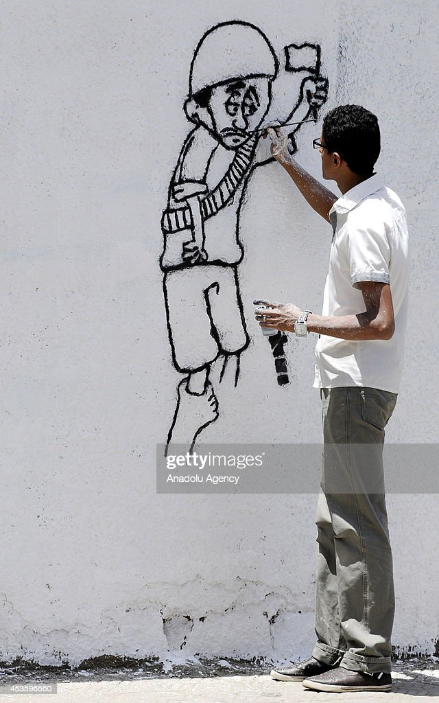 Graffiti artists draw the pictures of killed 14 Yemeni soldiers by al-Qaeda on the walls of Sanaa in Yemen, Sanaa on August 15, 2014.