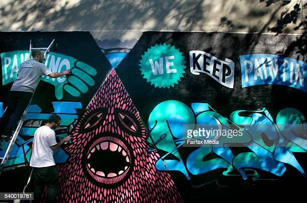 Graffiti artists Numskull and Beastman paint a legal mural on the side of a terrace house in Foveaux Street Surry Hills in Sydney Their work is in...