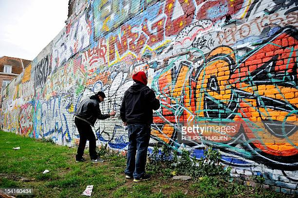 Graffiti artists paint on a wall on October 15 2012 in Lille northern France AFP PHOTO PHILIPPE HUGUEN