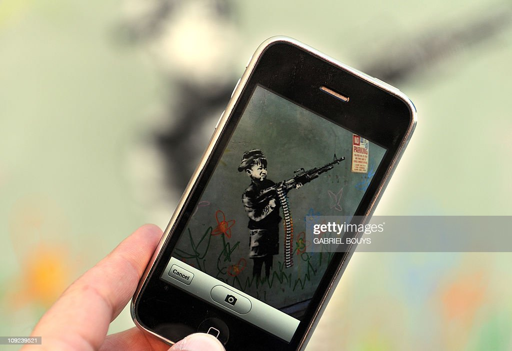 A graffiti attributed to secretive British artist Banksy depicting a child wielding a machine gun, in black and white surrounded by colored flowers, is spotted in Westwood, California on February 17, 2011. Another graffiti was ripped down Wednesday, February 16th in Hollywood, amid sightings of other pieces in a reported pre-Oscars publicity stunt. Banksy is nominated for best documentary for 'Exit Through the Gift Shop' at the Oscars, due to be announced on February 27th at the climax of Tinseltown's annual awards season.