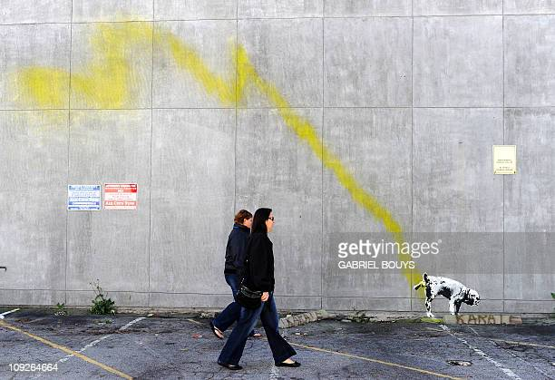A graffiti attributed to secretive British artist Banksy shows a dog urinating on a wall in Beverly Hills California on February 17 2011 Another...