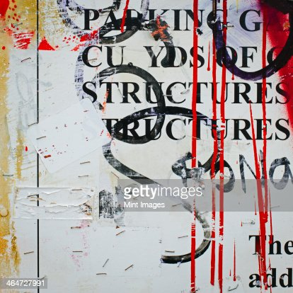 A graffiti covered wall in a city. Streaks of paint drips and printed messages covered with spray paint tags.