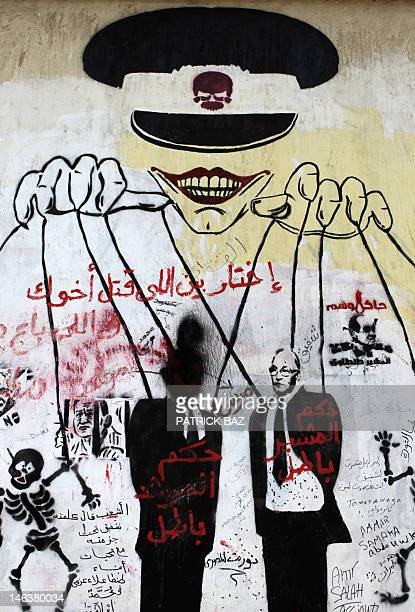 A graffiti depicting a ruling military puppeteer manipulating Egypt's presidential candidates Ahmed Shafiq and Mohamed Morsi appears on a wall in...