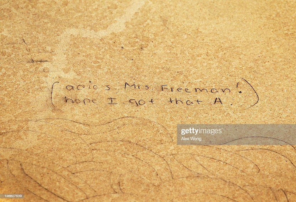 Graffiti is seen on one of the 857 empty school desks, representing the number of students nationwide who are dropping out every hour of every school day, is on display as an installation at the National Mall June 20, 2012 in Washington, DC. The installation was presented by not-for-profit organization College Board to call upon presidential candidates who are running for the White House to make education a more prominent issue in the 2012 campaigns and put the nation's schools back on track.