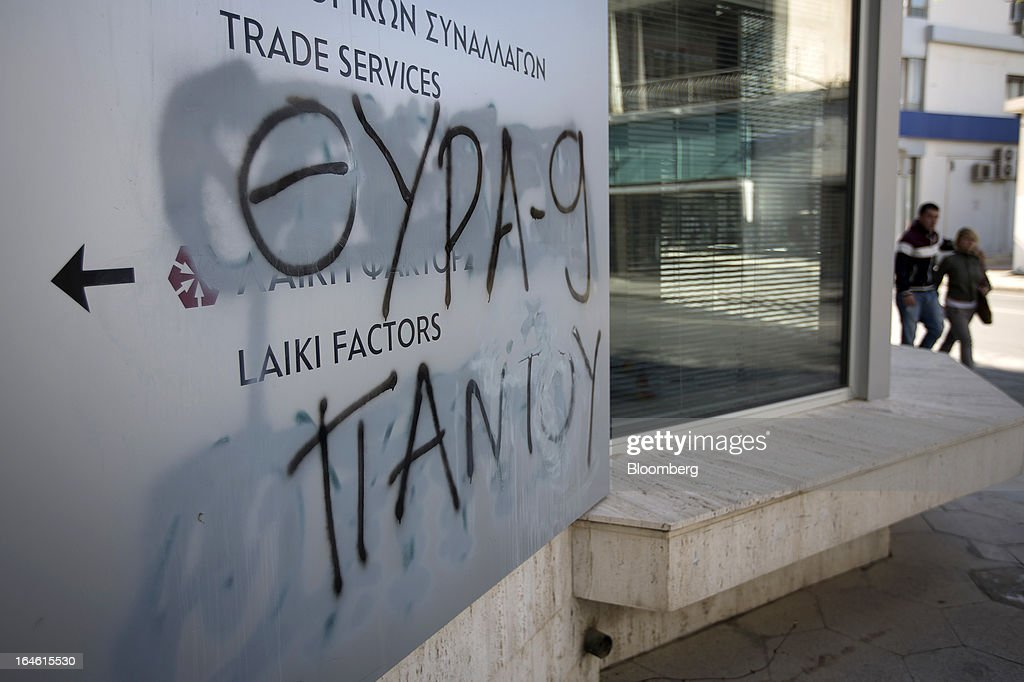 Graffiti is seen on the wall of a Cyprus Popular Bank Pcl, also known as Laiki Bank, branch in Nicosia, Cyprus, on Monday, March 25, 2013. Cyprus dodged a disorderly default and unprecedented exit from the euro by bowing to demands from creditors to shrink its banking system in exchange for 10 billion euros ($13 billion) of aid. Photographer: Simon Dawson/Bloomberg via Getty Images