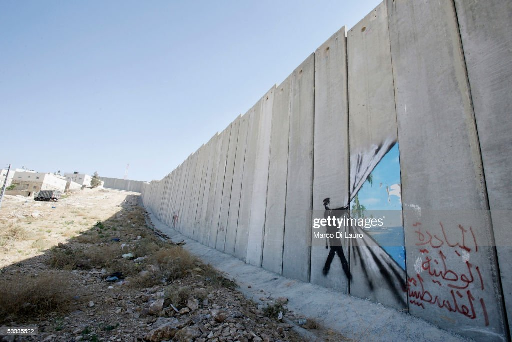 BANK - AUGUST 6. A graffiti made by the graffiti artist Banksy is seen on Israel's highly controversial West Bank barrier in Abu Dis on August 6, 2005. Banksy has made a name for himself with provocative images stencilled around the streets of London.On his recent trip to the Palestinian territories he has created nine of his images on Israel's highly controversial West Bank barrier.