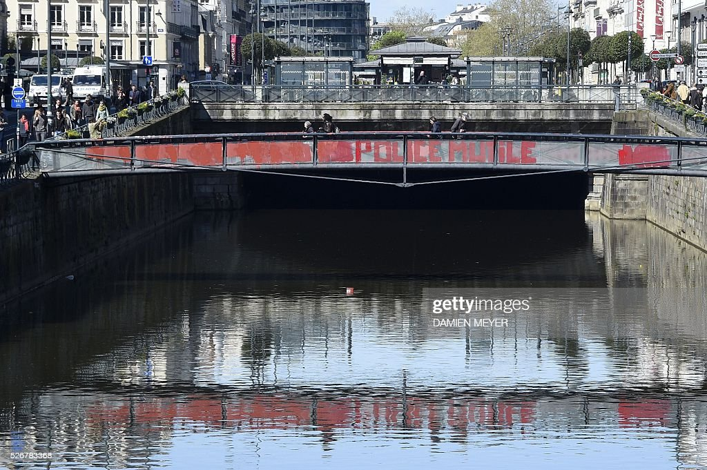Graffitti on a bridge reads 'Police mutiliate' near the site where a 20-year-old student lost vision in one eye during a demonstration on April 28, in Rennes, western France, on May 1, 2016. / AFP / DAMIEN