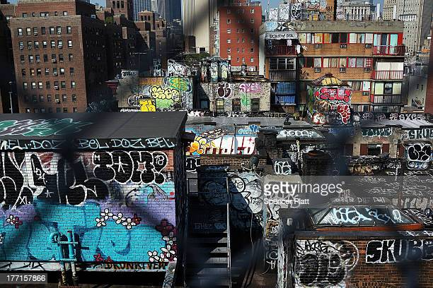 Graffiti painted building stand below the Manhattan Bridge on August 21 2013 in New York City The island of Manhattan is connected to the mainland by...
