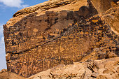 Neolithic graffiti art on a stand-alone rock in the desert