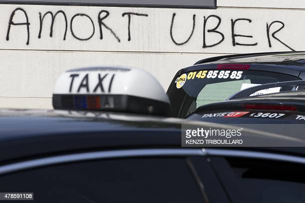 Graffiti that reads ' Death to Uber' as taxi vehicles block Porte Maillot west Paris on June 26 as drivers react furiously at what they see as unfair...