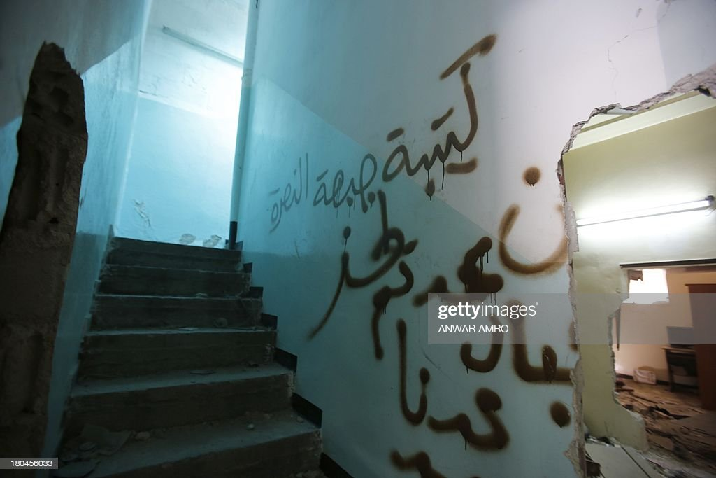 Graffiti thats reads in Arabic, 'al-Nusra Front' , a Jihadist group, is daubed along the wall of a stair well in a buidling once held by rebel forces and now captured by the Popular Front for the Liberation of Palestine General Command (PFLP-GC) in the Yarmuk refugee camp in the Syrian capital Damascus on September 12, 2013. Arriving at the rubble of the Palestinian Yarmuk refugee camp in Damascus, Hadia al-Fut discovered that her husband had been killed while fighting in the ranks of a pro-regime Palestinian group. The PFLP-GC has been allied to Syrian President Bashar al-Assad's government whose troops have been fighting rebel forces for the past two years.