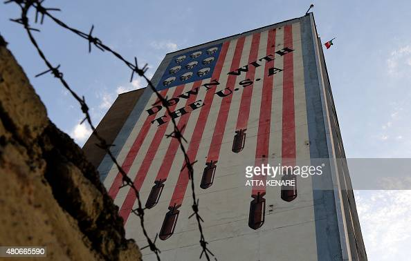 Graffiti with antiUS slogan is seen decorating the wall of a building in Tehran on July 14 2015 President Hassan Rouhani told Iranians that 'all our...