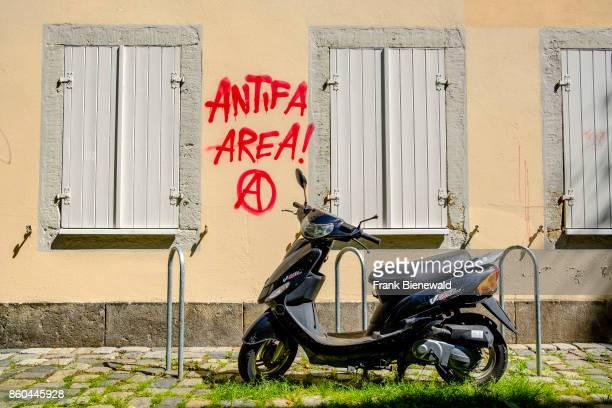 Graffiti with the saying Antifa Area is sprayed at a house wall in the township Neustadt a black scooter parked in front
