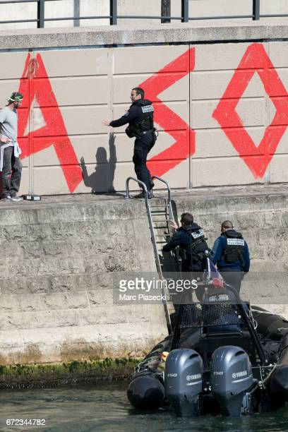 Graffitists are arrested by french policemen on the banks of the river Seine while painting 'De La Resignation Individualiste a l'Ambition De La...