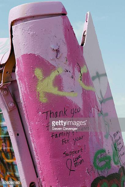 Graffitti in support of finding a cure for cancer affecting women decorates on of the cars in the Cadillac Ranch The cars were recently painted pink...