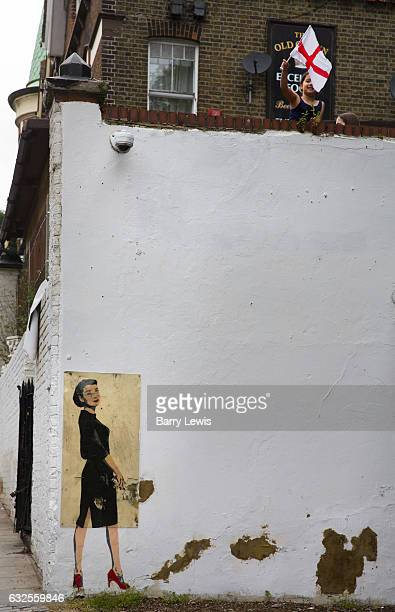 Graffitti of Audrey Hepburn on London pub wall protected by plastic with child waving a George Flag on 10th June 2016 Highgate London