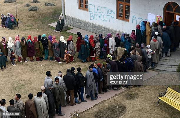 Grafitti calling for the boycott of state assembly elections are seen spraypainted on the wall of a polling station as Kashmiri voters queue in...