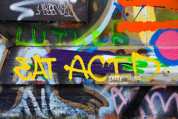 Grafitti on side of building wall says 'eat acid'