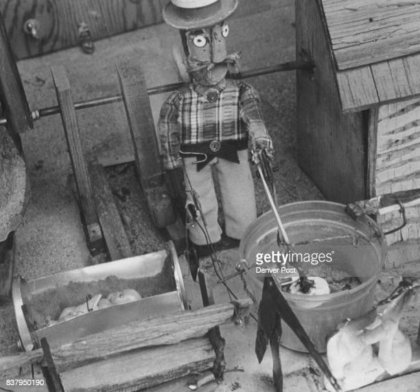 Gragg FM Toy Mechanic A farmer operates butter churn rocks a baby and washes clothes all at same time Credit Denver Post