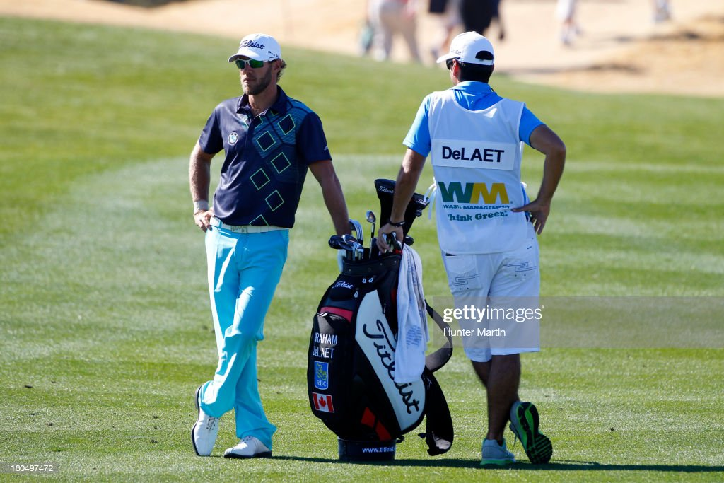 Graham DeLaet of Canada stands in the fairway with his caddie on the ninth hole during the second round of the Waste Management Phoenix Open at TPC Scottsdale on February 1, 2013 in Scottsdale, Arizona.