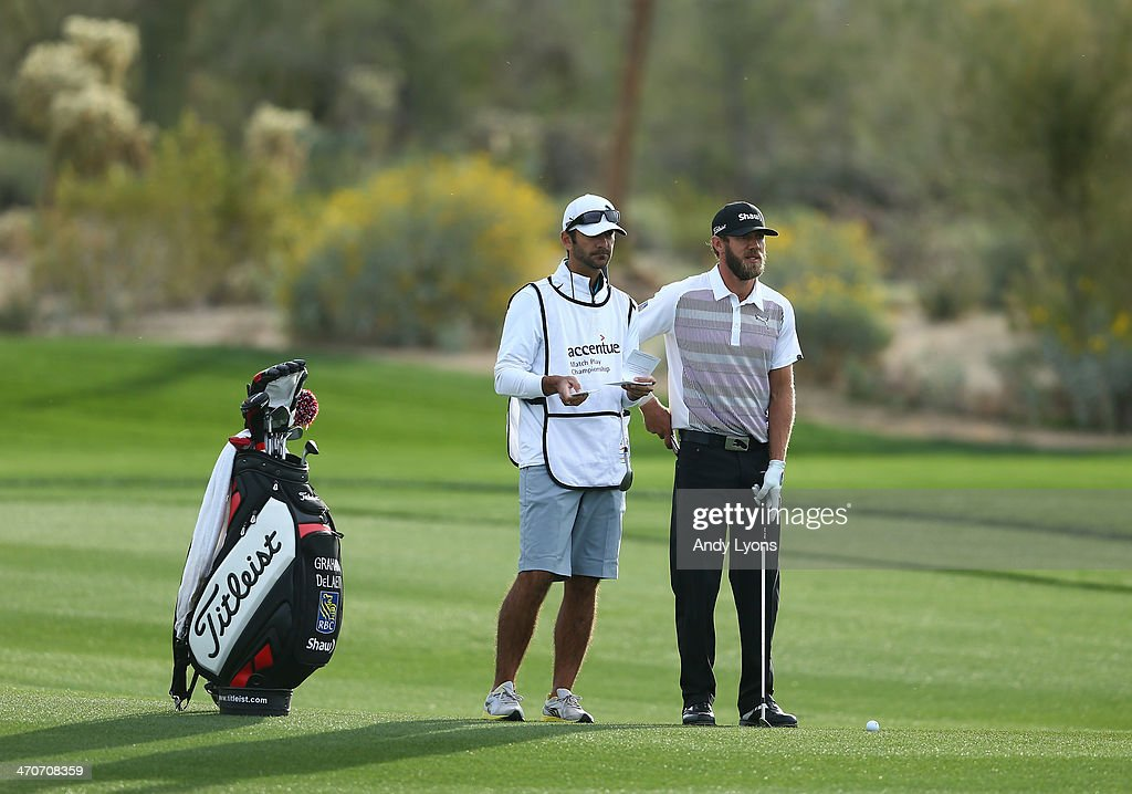 Graham DeLaet of Canada stands with his caddie before playing a shot during the first round of the World Golf Championships - Accenture Match Play Championship at The Golf Club at Dove Mountain on February 19, 2014 in Marana, Arizona.