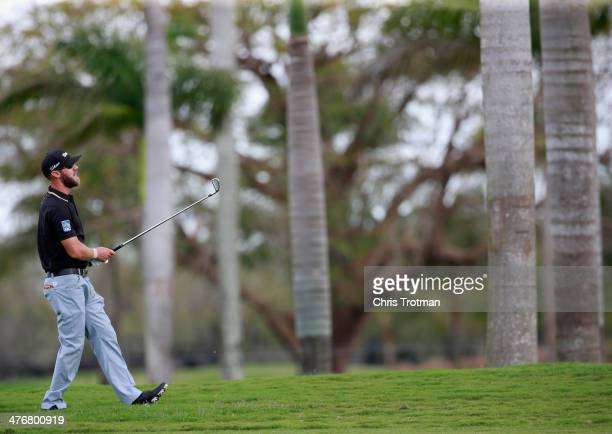 Graham DeLaet of Canada watches a shot during a practice round prior to the start of the World Golf ChampionshipsCadillac Championship at Trump...