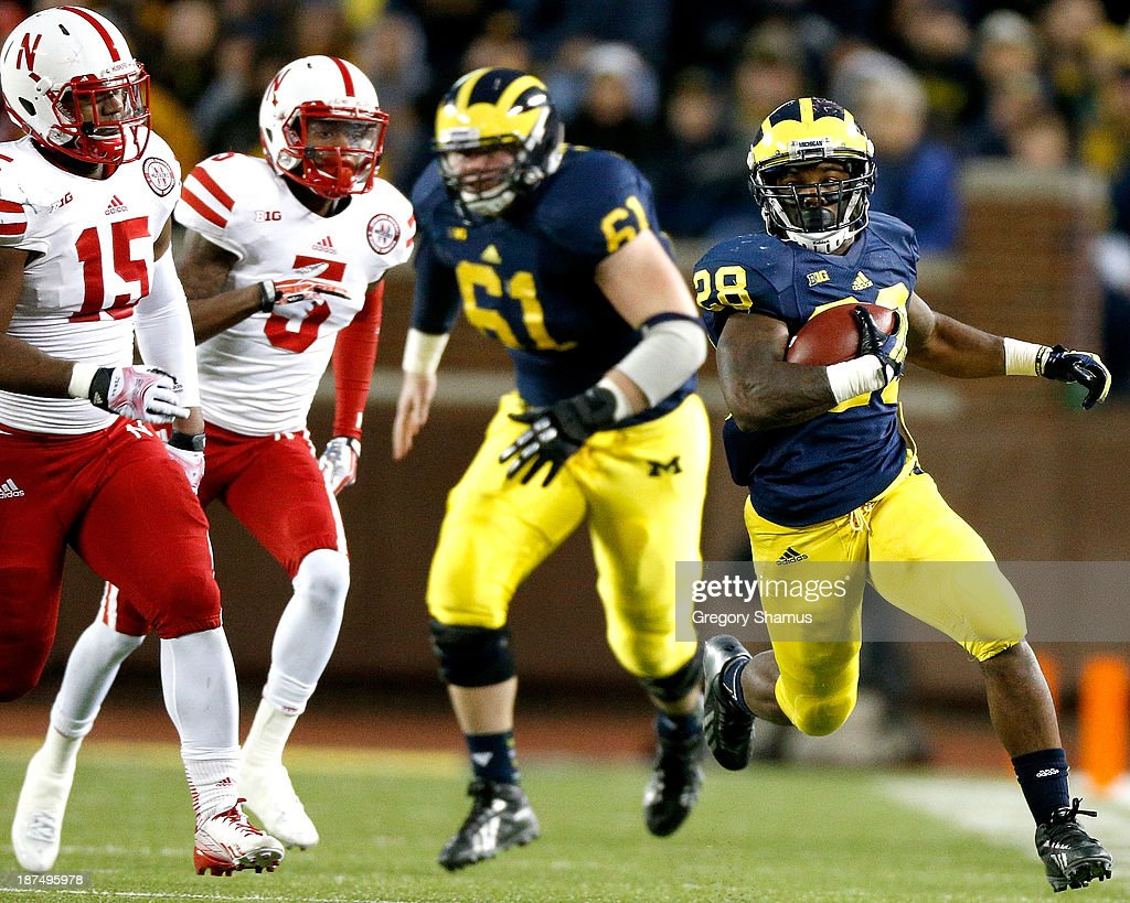 Graham Glasgow #61 of the Michigan Wolverines blocks for Fitzgerald Toussaint #28 against Michael Rose #15 and Josh Mitchell #5 of the Nebraska Cornhuskers during the third quarter at Michigan Stadium on November 9, 2013 in Ann Arbor, Michigan.