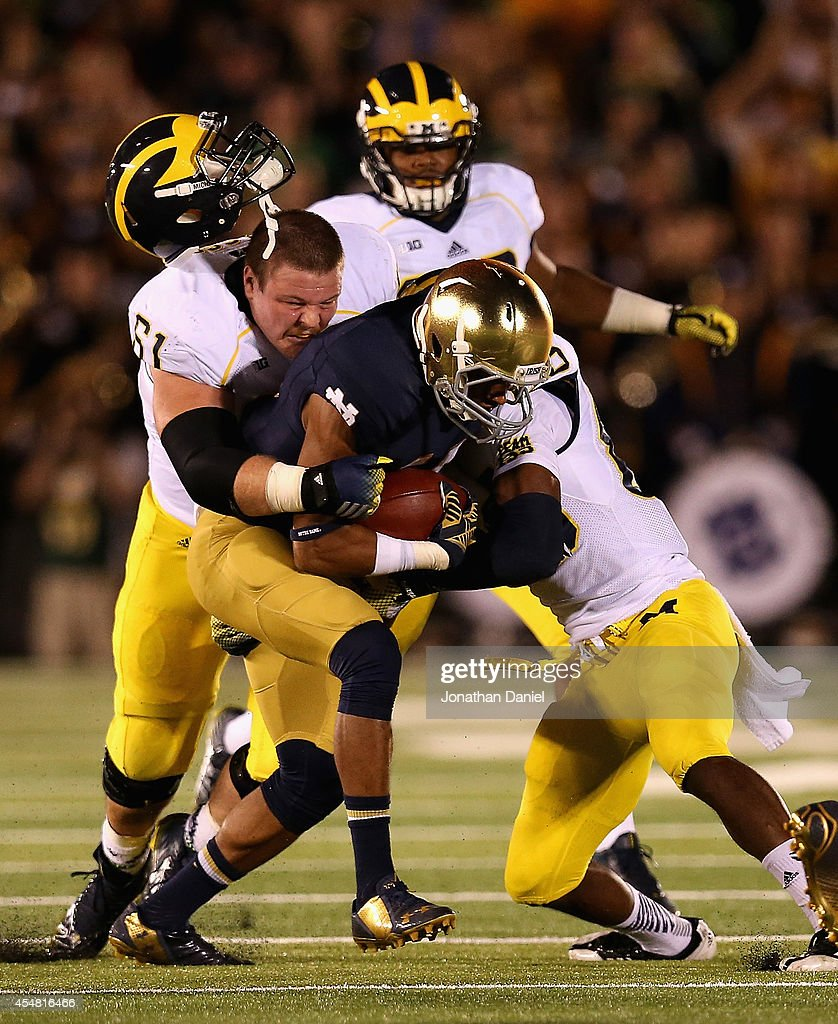 Graham Glasgow of the Michigan Wolverines looses his helmet as he and teamate Jehu Chesson try to tackle Max Redfield of the Notre Dame Fighting...