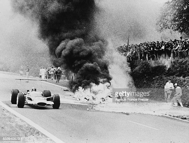 Graham Hill driving the Gold Leaf Team Lotus 49B passes the fire from the burning magnesium chassis Honda Racing Honda RA302 Honda V8 of Jo Schlesser...