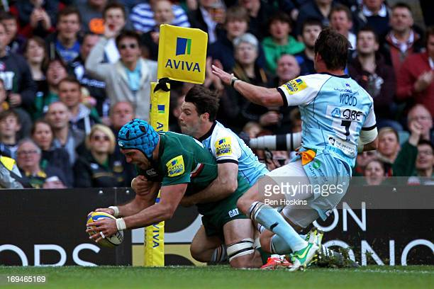 Graham Kitchener of Leicester dives over to score his team's second try despite the tackle from Ben Foden of Northampton during the Aviva Premiership...