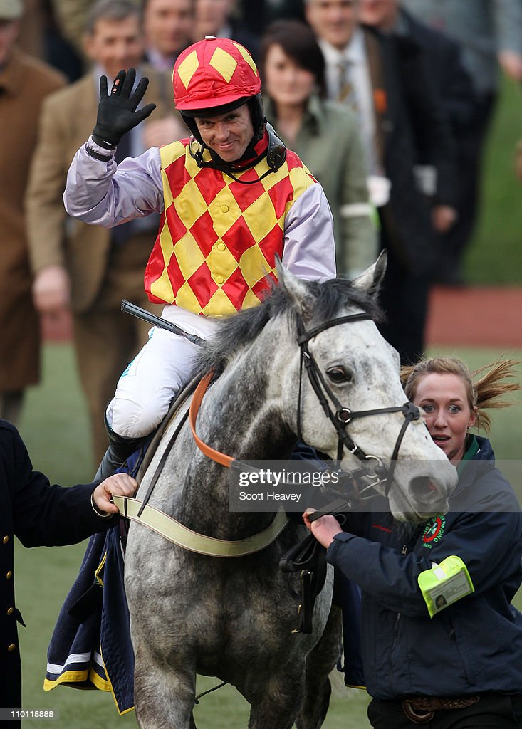 Graham Lee celebrates after winning the 515 Centenary Novices' Handicap Steeple Chase on Divers at Cheltenham Racecourse on March 15 2011 in...