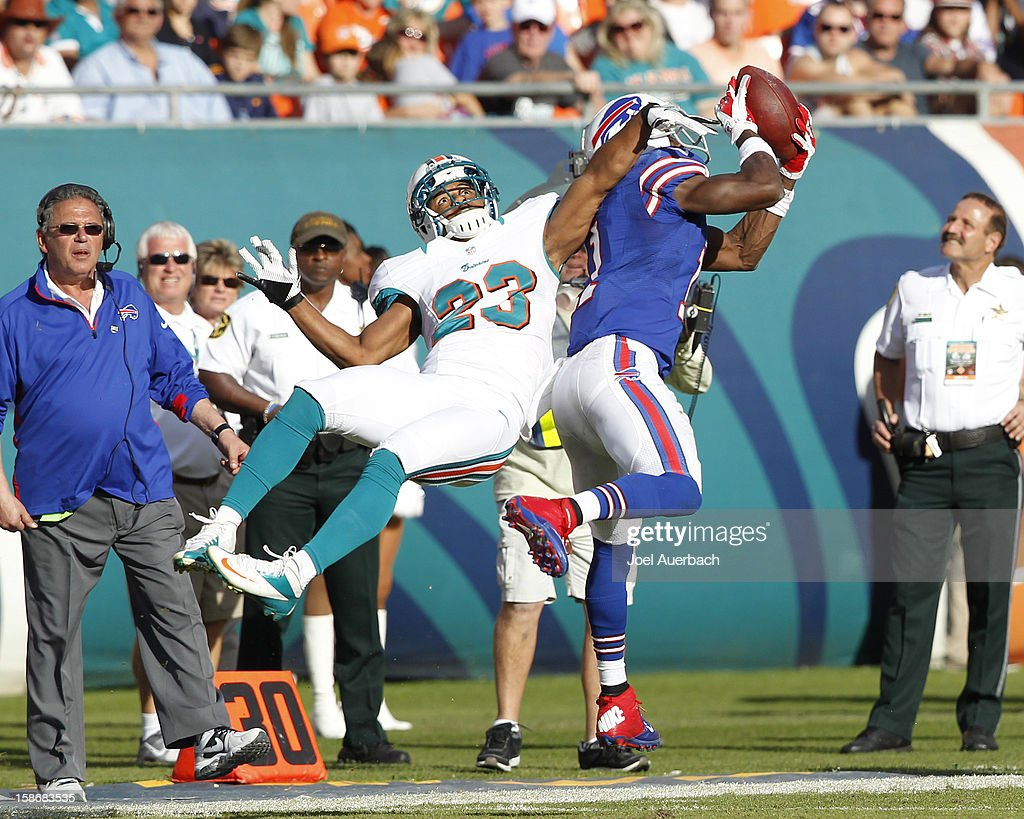 T.J. Graham #11 of the Buffalo Bills catches the ball while being defended by Bryan McCann #23 of the Miami Dolphins on December 23, 2012 at Sun Life Stadium in Miami Gardens, Florida. The Dolphins defeated the Bills 24-10.