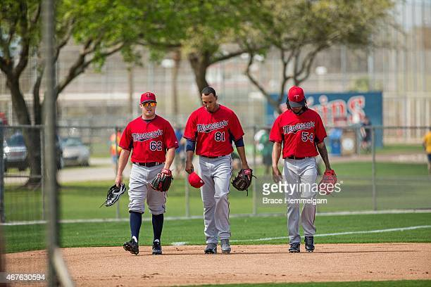 R Graham of the Minnesota Twins walks with Adrian Salcedo and Ervin Santana on March 2 2015 at the CenturyLink Sports Complex in Fort Myers Florida