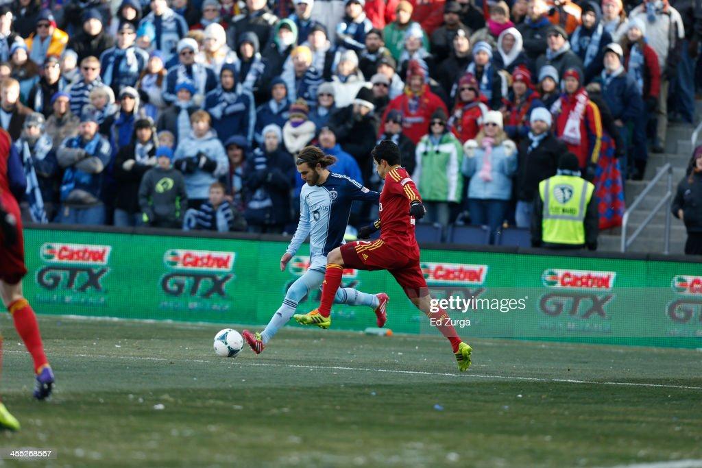 Graham Zusi of Sporting Kansas City kicks the ball away from Tony Beltran of Real Salt Lake during the MLS Cup Final at Sporting Park on December 7...