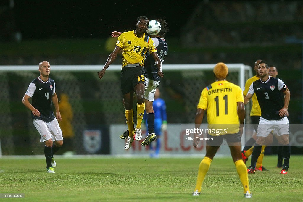 Graham Zusi #19 of the United States and Tamorley Thomas #13 of Antigua and Barbuda go for a header during a World Cup Qualifying game at Sir Vivian Richards Stadium on October 12, 2012 in Antigua, Antigua and Barbuda.