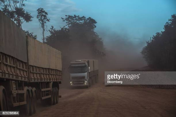Grain delivery trucks ride along the BR163 Highway as dust obscures visibility in Moraes Almeida Para State Brazil on Friday July 21 2017...