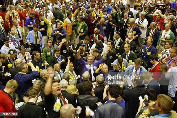 Grain traders signal offers in the corn futures pit at the Chicago Board of Trade May 12 2004 in Chicago Illinois Despite expected large yields corn...