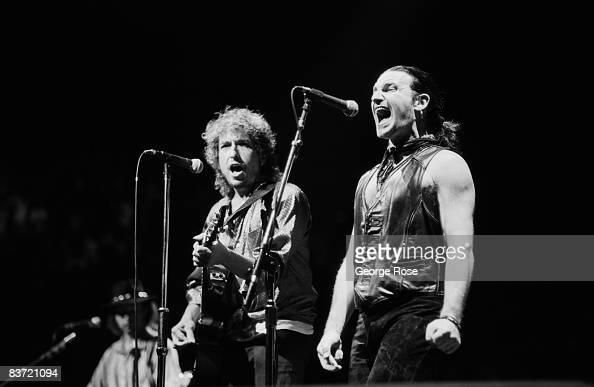 Grammy Awardwinning singer Bono of the rock group U2 performs songs from 'The Joshua Tree' album with folk singer Bob Dylan during a 1987 Inglewood...