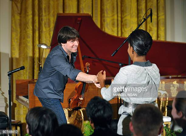 Grammy Awardwinning violinist Joshua Bell shakes hands with US First Lady Michelle Obama after performing at a classical music student workshop...