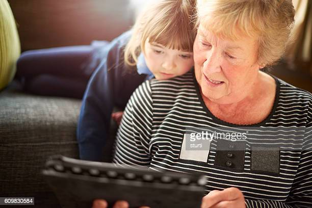 gran and granddaughter looking at a digital tablet .