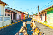 Site seeing by horse carriage the old city Granada in Nicaragua. Colorful facades against blue sky.