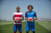 Granada CF football team's new players Mexican goalkeeper Guillermo Ochoa and Brazilian defender Gabriel Silva pose on the pitch during their...