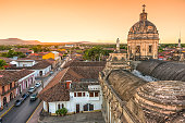 Skyline of old city Granada in Nicaragua at sunset. View from bell tower on colorful houses and street with some cars and unrecognizable people.