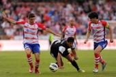 Granada's Brazilian defender Guilherme Siqueira and defender Diego Mainz vie with Malaga's Paraguayan forward Roque Santa Cruz during the Spanish...