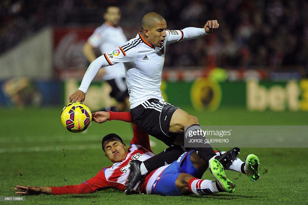 Granada's Colombian forward Jeison Murillo vies with Valencia's French midfielder Sofiane Feghouli during the Spanish league football match Granada...
