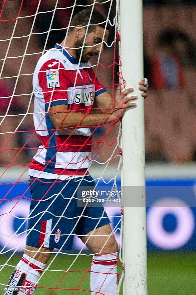 Granada's defender David Rodriguez Lomban grabs the goal's post during the Spanish league football match Granada FC VS Club Atletico de Madrid at...