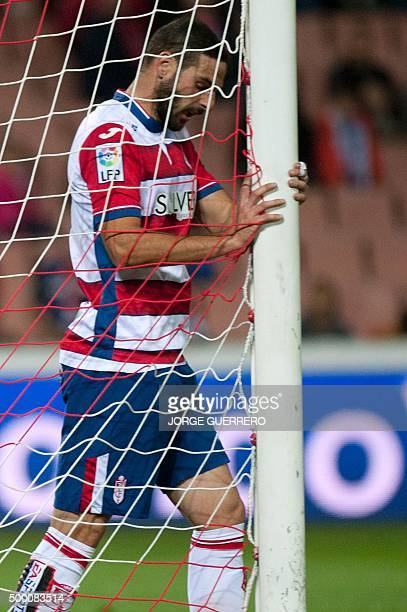 Granada's defender David Rodriguez Lomban grabs the goal's post during the Spanish league football match Granada FC VS Club Atletico de Madrid at...